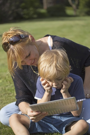 Photo pour Son using touchscreen tablet PC with his mother  The boy holds his head in his hands  - image libre de droit