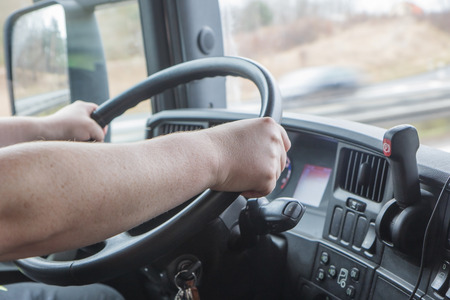 Foto de Closeup view of the hands of truck driver who is holding the steering wheel. Photo shooted in the vehicle cabin. - Imagen libre de derechos