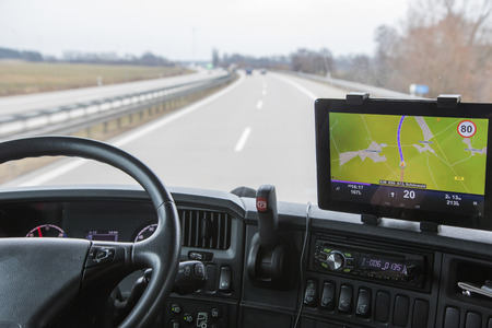 View of highway traffic through the windshield of the truck cab. Navigation is mounted on the dashboard.