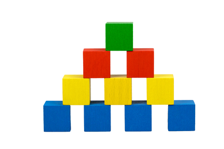 Pyramid built from wooden colorful cubes with gubs isolated on a white background. Bottom line consists of blue cubes over which there are three yellow cubes over which there are two red cubes on top is green cube.