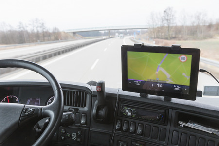 Photo pour Inside the cab of the truck while driving. Focused on the tablet with navigation. The map is intentionally slightly out of focus. All potential trademarks are removed - image libre de droit