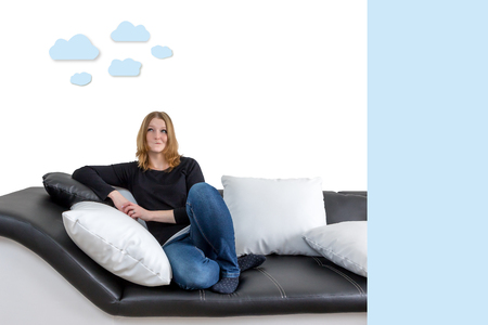 Grinning long haired young woman is sitting on a black and white couch with black and white pillows. Woman is looking upwards on the illustration of clouds in the background. Empty blue rectangle is ready for your text.