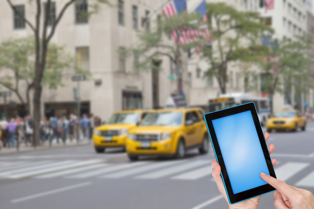 Photo pour Female finger touching tablet blue blank touchscreen ready for your text. Intentionally blurred image of a Fifth Avenue (NYC) is in the background. All potential trademarks are removed. - image libre de droit