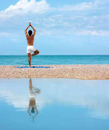 Photo pour Man Practicing Yoga near the Sea and Reflected on Water - image libre de droit