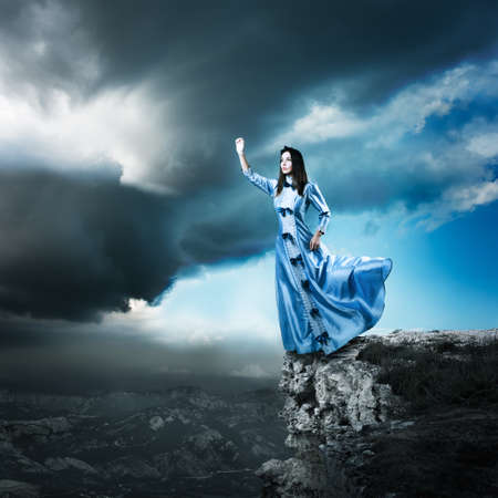 Full Length Photo of Fantasy Woman in Waving Blue Dress Reaching for the Light. Dramatic Moody Sky. HDR Cloudscape.