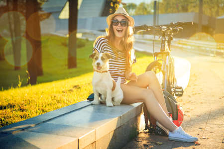 Foto de Happy Hipster Girl with her Dog and Bike in the City. Toned and Filtered Photo. Modern Youth Lifestyle Concept. - Imagen libre de derechos