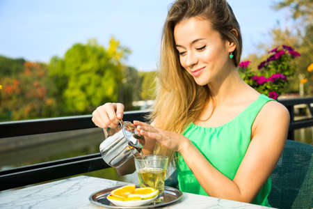 Happy Smiling Woman Making Green Tea Outdoors. Summer Background. Healthy Eating Concept. Shallow Depth of Field.
