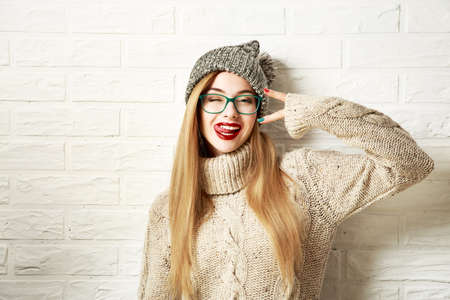 Photo pour Funny Hipster Girl in Knitted Sweater and Beanie Hat Going Crazy at White Brick Wall Background. Trendy Casual Fashion Outfit in Winter. Toned Photo with Copy Space. - image libre de droit