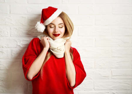 Smiling Christmas Girl with Closed Eyes in Red Winter Clothes at White Brick Wall Background. Romantic Dreaming Woman Portrait. Toned Photo with Copy Space.の写真素材