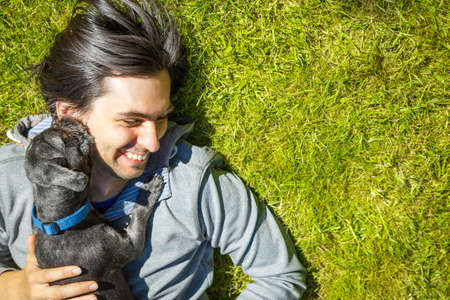 Photo pour Little Dog and His Happy Owner Having Fun and Lying on Green Grass. Pets Love and Playing Concept. Copy Space. - image libre de droit
