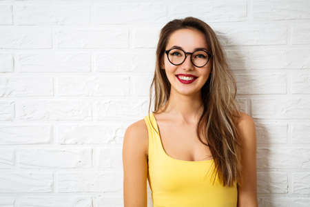 Foto de Happy Smiling Hipster Girl in Glasses at White Brick Wall Background. Summer Street Style Fashion Outfit. Copy Space. - Imagen libre de derechos