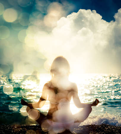 Photo pour Woman Practicing Yoga by the Sea. Silhouette of a Slim Girl. Nature Background with Sunlight Bokeh. Meditation, Spiritual and Soul Concept. Healthy Lifestyle. Double Exposure Filtered Photo. - image libre de droit