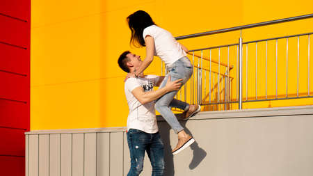Photo for Happy man carrying his girlfriend on yellow background - couple in love - Royalty Free Image