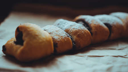 Foto für Freshly Baked Chocolate Rolls with a delicious filling, sprinkled with powdered sugar. Against the background of brown craft paper - Lizenzfreies Bild