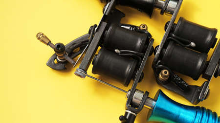 Photo for Two tattoo machines on a yellow background - tattoo industry - Royalty Free Image