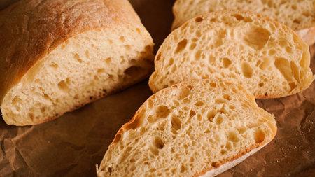 Foto für Ciabatta slices on craft paper. Fresh delicious pastries. Fresh homemade bread. - Lizenzfreies Bild