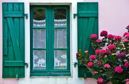 Photo pour Sunny view of a window with green shutters and a pink house wall, in which a crocheted, white curtain hangs - image libre de droit
