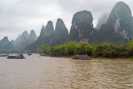 Photo for Busy traffic on the Li River near Xingpingzhen fishing village in the vicinity of Yangshuo near Guilin - Royalty Free Image
