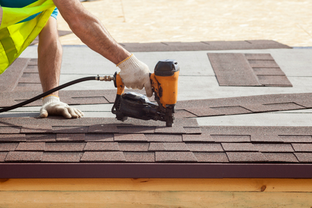 Photo pour Construction worker putting the asphalt roofing (shingles) with nail gun on a new frame house - image libre de droit