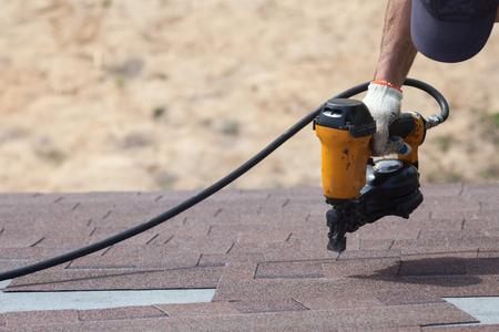Foto de Roofer builder worker with nailgun installing Asphalt Shingles or Bitumen Tiles on a new house under construction - Imagen libre de derechos