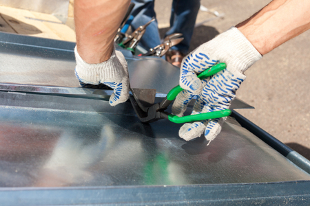 Foto per Roofer folding a metal sheet using special pliers with a large flat grip - Immagine Royalty Free
