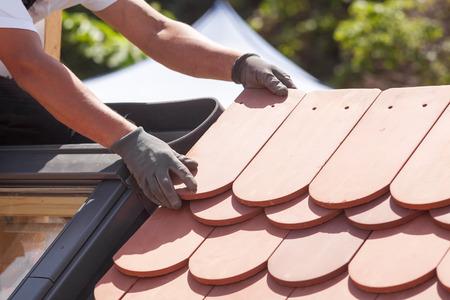 Foto de Hands of roofer laying tile on the roof. Installing natural red tile. - Imagen libre de derechos