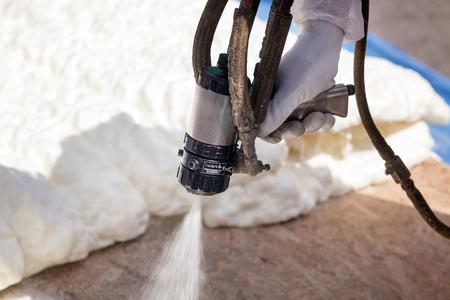 Photo pour Technician spraying foam insulation using Plural Component Spray Gun - image libre de droit