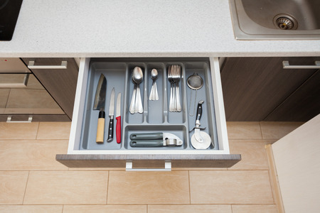 Photo pour High angle top view photo of clean white cook worktop table and open new modern wooden kitchen drawer with different cutlery spoon, knife, fork and stuff - image libre de droit