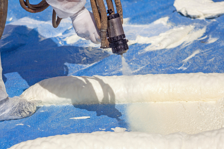 Photo pour Technician dressed in a protective white uniform spraying foam insulation using Plural Component Spray Gun. Spraying polyurethane foam for roof and energy saving - image libre de droit