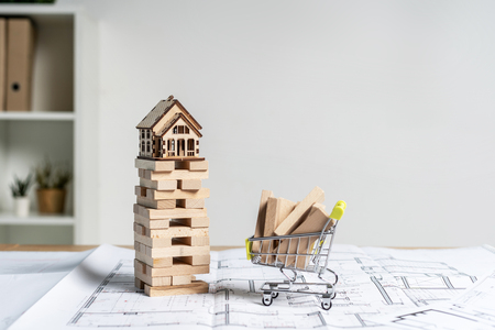 Foto de Little wooden house on top of  blocks with wood element or building plank board in small shopping cart stand on table inside bright workstation with copy space for text - Imagen libre de derechos