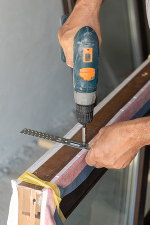 Plastic window frame assembly concept. Cropped close up and vertical photo of adult workman using torque screwdriver installing metal anchor plate on new window frame