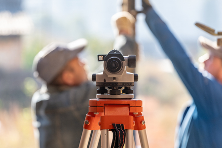 Formwork construction concept. Optical level against blurred background with cooperation between two adult workman working on incomplete object