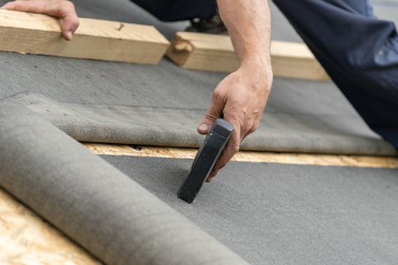 Close up, cropped photo of professional, qualified workmen working working with special waterproof bitumen membrane on wooden roof top with osb or plywood panel under new modern building construction