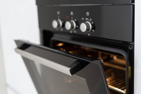 Photo pour Selective focus of black and modern built in oven with open glass door on white contemporary kitchen - image libre de droit
