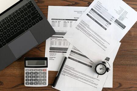 Foto de Top view of laptop computer, documents, financial bills, alarm clock, calculator and stationery on wooden table in office - Imagen libre de derechos
