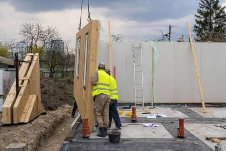 Foto de Process of construction new and modern modular house from composite sip panels. Two worker man in special protective uniform wear working on building development industry of energy efficient property - Imagen libre de derechos