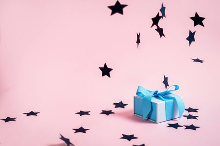 Foto de Happy anniversary! Small blue wrapped gift box with beautiful bow isolated against pastel pink background with copy or empty space for text and paper stars decorations - Imagen libre de derechos