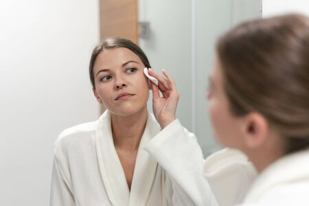 Photo pour woman in white bathrobe holding cotton pad in hands, looking at mirror in bathroom and remove make up from face - image libre de droit