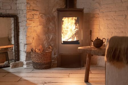 Photo for Table and teapot near wood stove fireplace in comfort house with cozy interior in room. Wicker basket with firewood near chimney with metal body and glass door - Royalty Free Image