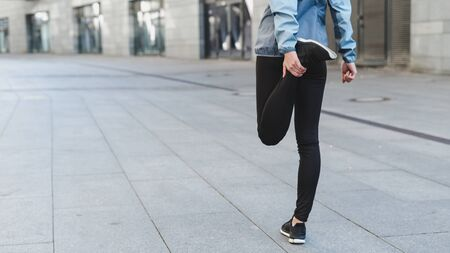 Photo pour Cropped and back view of young adult woman, stretching before cardio workout. Sportsman girl in sportswear and sneakers shoes spending day on sport training outdoor in city - image libre de droit