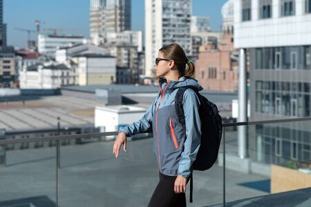 Photo pour Side view of young adult woman in casual street style outfit with backpack spending weekend day outdoor in city, looking away - image libre de droit