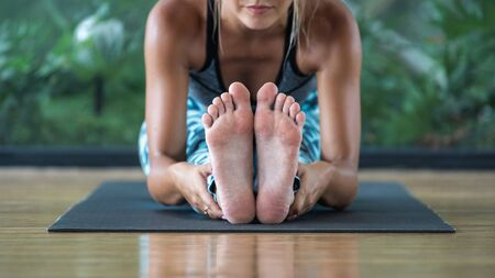 Panoramic and selective focus of young adult girl feet. Barefoot woman sitting in head to knee forward bend position, making yoga exercise, training on mat against natural plants on background