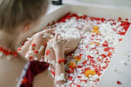 Photo pour Natural skin care concept. Selective focus on woman legs in bathtub with tropical flowers. Young adult girl lying in bath and enjoying spa procedure - image libre de droit