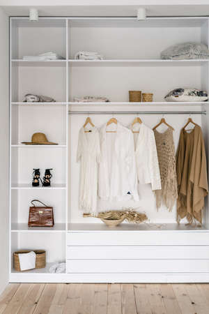 Photo pour Vertical photo of modern and open garderobe in dressing room with woman casual clothes wear, accessories, shoes and handbag on shelf - image libre de droit