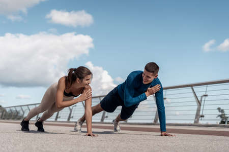 Photo pour Morning workout concept. Happy adult athlete woman and man doing shoulder tap exercise, standing in plank pose, making sport training outdoors together - image libre de droit