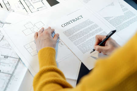 Photo for High angle view of woman reading contract, sitting behind table with project plan, analyzing real estate market, mortgage loan with low rate and signing agreement for buying property - Royalty Free Image