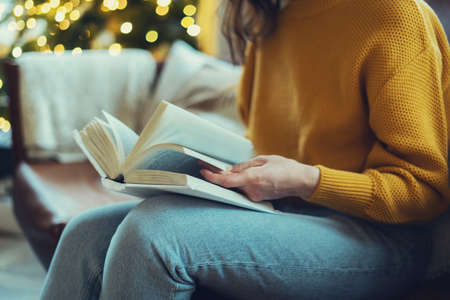 Photo pour Concept of leisure and hobby. Cropped view of young woman reading paper book, turning pages, enjoying new interesting story, spending weekend at cozy home, sitting on comfortable couch in living room - image libre de droit