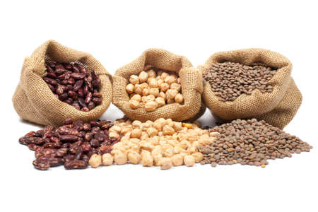 Lentils, chickpeas and red beans spilling out over a white background.