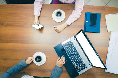 Photo for Coffee break at the Desk in the office. Hands of young girls on the desktop with a laptop and smartphone. The view from the top. - Royalty Free Image
