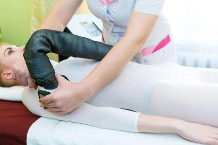 Photo pour A young woman is doing anti-cellulite LPG massage to correct the body shape. - image libre de droit